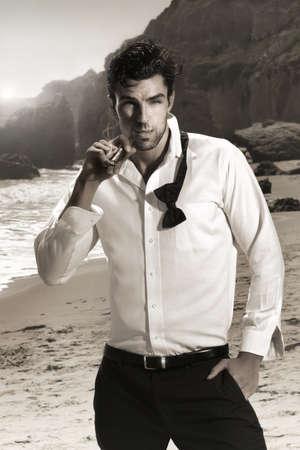 Konzept Mode Porträt einer sexy gefährlich zuversichtlich, männliches Modell in gelockert bow-tie Zigarre rauchen in exotischen Umgebung mit leichten Sepia getönten Vintage-Look