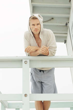 Portrait of a young male model in board shorts and warm pullover relaxing in outdoor beach setting Stock Photo