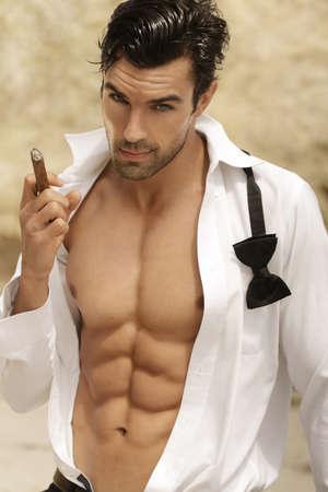 homme nu: Sexy cigare mâle fumer modèle en tenue de soirée ouverte exposant grand corps tonique musculaire et abs Banque d'images