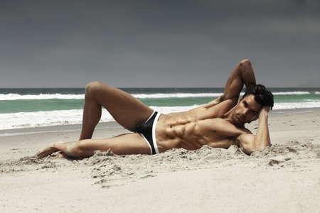 Fashion portrait of a sensual gorgeous male model in swimwear posing on beach Stock Photo - 13931717