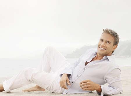 明るい屋外ファッション ライフ スタイル肖像画いいと素晴らしい見ている若い男性モデルの幸せな笑顔、古典的なカジュアルな服に横たわる 写真素材