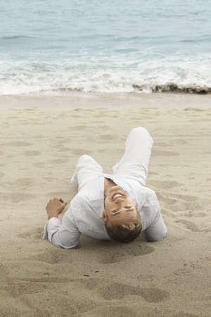 laying down: Fun outdoor portrait of a young smiling man on the beach looking back Stock Photo