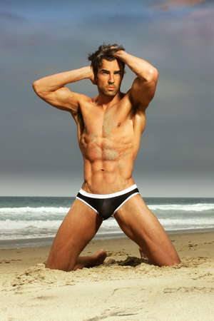 naked youth: Sexy male model in fashion swimwear posing on the beach