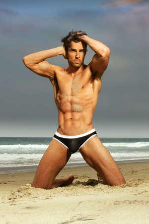uomo nudo: Sexy modello maschile in costume da bagno di moda in posa sulla spiaggia Archivio Fotografico
