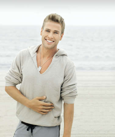 Outside portrait of a good-looking young male model smiling on the beach with copy space photo