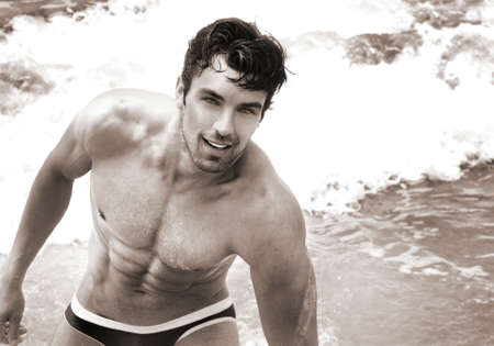 beach hunk: Fine art sepia toned portrait of beautiful young fit man at the beach Stock Photo