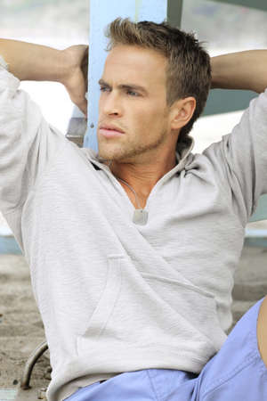Good-looking young man outdoors looking off to the left in casual clothing photo