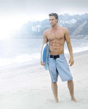 hombre sin camisa: Retrato estilizado de un gran hombre en busca joven con tabla de surf en la playa con un tono general de color azul para el efecto