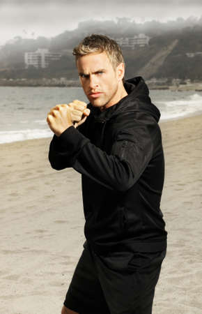 determined: Beach portrait of an active young athlete in boxing stance with fists up