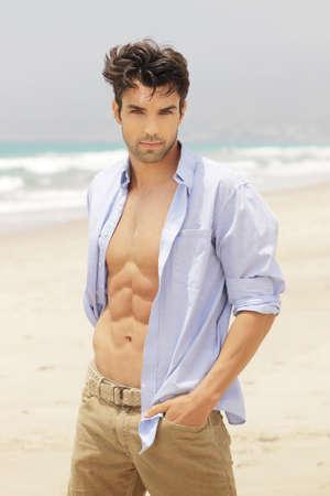 Goed uitziende man op het strand met open hemd Stockfoto