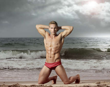 Good looking young fit man posing on dramatic beach scene in red swimwear Stock Photo