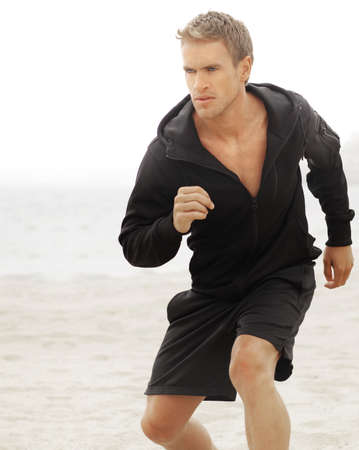 Young athletic man running with determined expression photo