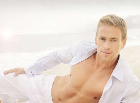 male grooming: Succesful young good-looking guy on the beach with relaxed open shirt Stock Photo