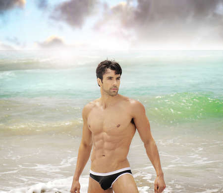 Beautiful male model in sexy swimwear in the ocean at beach photo