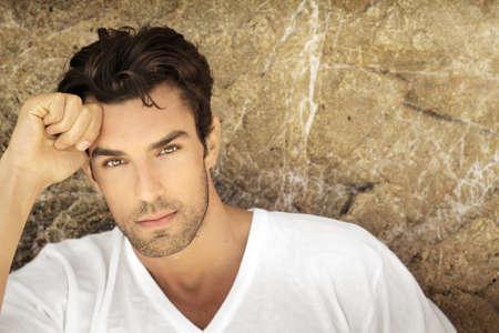 야외에서 자연 배경에 흰색 캐주얼 셔츠에 매우 잘 생긴 얼굴을 가진 젊은 남자의 초상화입니다