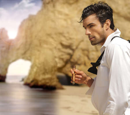 bachelor: Sexy masculine man in formal clothes smoking cigar on exotic beach