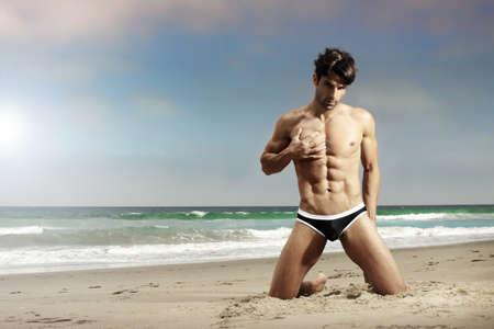 nue plage: Sensuelle mod�le masculin pose sur la plage avec du sable et l'oc�an