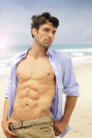 open shirt: Good looking young fit male on beach with open shirt and muscular body with abs Stock Photo