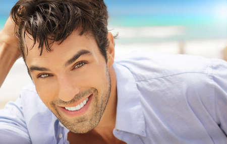 Great looking young man outdoors with big happy smile  photo