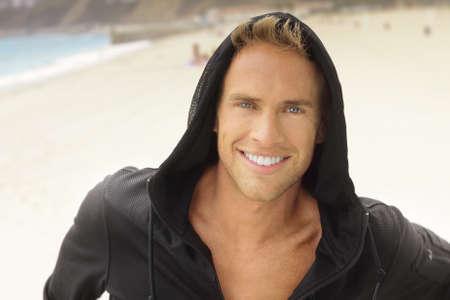jeune mec: Jeune homme avec grand sourire � la plage dans le capot du sport actif