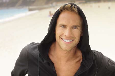 Young guy with great smile at the beach in active sportswear hood Imagens
