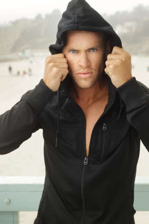determined: Intense young man in black hooded workout clothing outdoors Stock Photo
