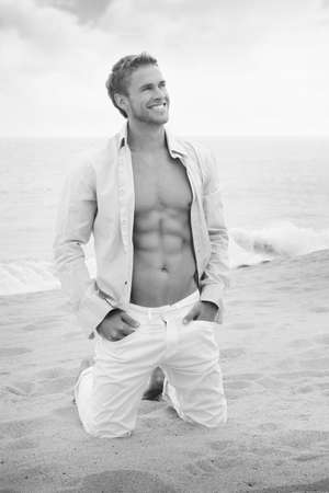 Classic fine art black and white portrait of a relaxed young man with open shirt on vacation at beach photo