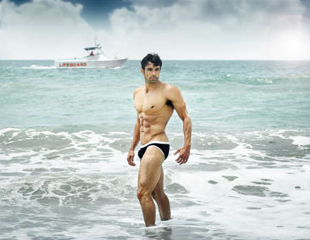 naked abs: Good looking guy standing in the ocean with boat in background