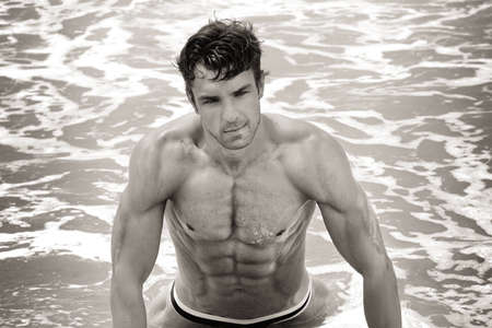 beach hunk: Fine art sepia toned portrait of a beautiful muscular shirtless man in the water