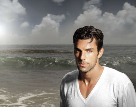 good grooming: Fashion portrait of a handsome man against ocean background