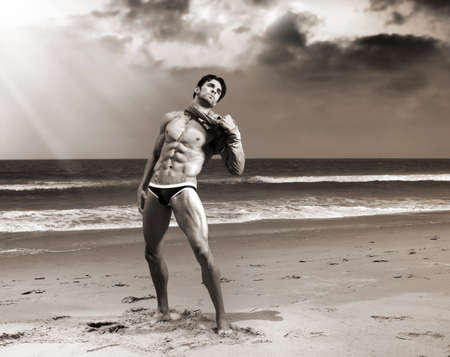 nude art model: Fine art body portrait of a beautiful muscular man on the beach with dramatic sky and sepia toning Stock Photo
