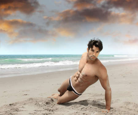 naked man: Fit young man posing on the beach in sexy swimwear Stock Photo