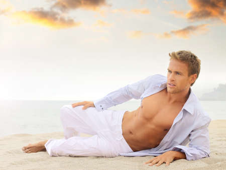 Beach portrait of a good looking young blond man in white pants and light blue shirt laying down looking off  photo