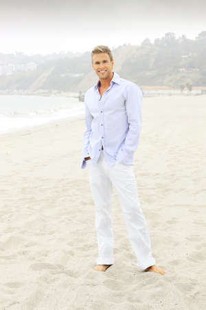 Relaxed smiling man in white pants and elegant blue shirt and bare feet on the beach Фото со стока