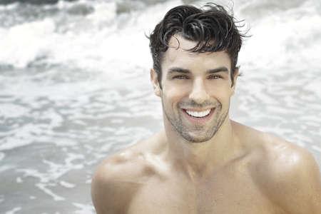 Knappe gelukkige man glimlachend met oceaan water achtergrond Stockfoto