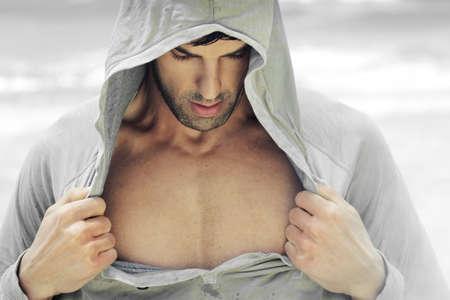 hombres sin camisa: Hombre sexy en ropa deportiva con capucha revelando su pecho musculoso