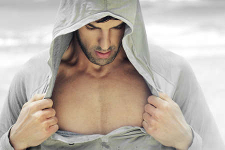 male grooming: Sexy man in hooded activewear revealing his muscular chest