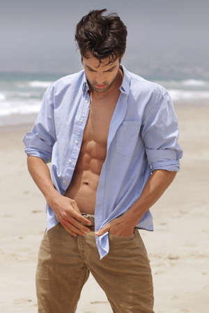 head down: Beach portrait of a fit attractive man looking down with open shirt Stock Photo