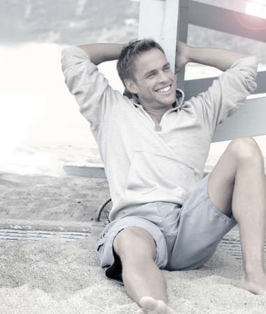 Stylized lifestyle portrait of a happy young man laughing and relaxing on the beach with an overall blue toning for cool effect photo