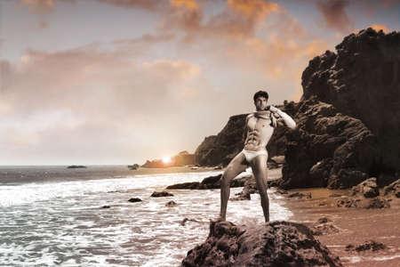 Fine art hand toned landscape portrait of a sexy male model against exotic beach scenic