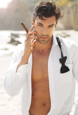 Great looking sexy male model with open white shirt and loose bow tie smoking cigar on beach Stock Photo - 14250926
