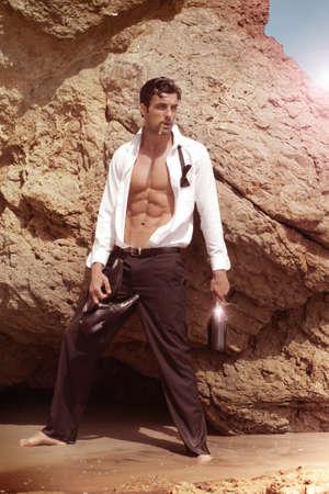vintage look: Moda ritratto di un modello sexy maschile allentato bow-tie sigaro tenendo bottiglia di champagne in ambiente esotico, con retro look vintage Archivio Fotografico