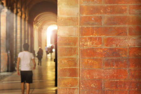 People walking through ancient arched walk way with brick wall Фото со стока