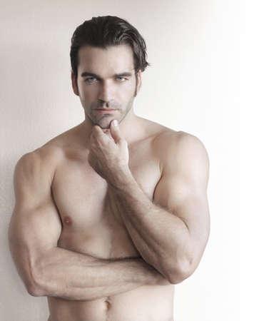 naked man: Hombre sin camisa joven con la mano a la barbilla contra el fondo neutro