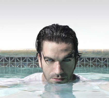 looker: Sexy male model in swimming pool with copy space above Stock Photo