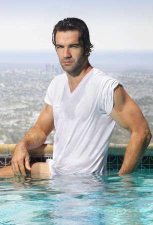 muscle shirt: Hombre sexy joven en camiseta mojada en la piscina con vistas vistas a la ciudad Foto de archivo