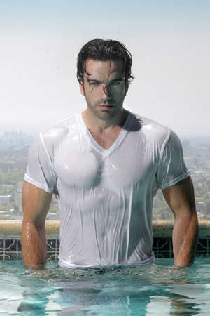 tee: Fashion portrait of a gorgeous male model in soaked wet t-shirt standing in luxurious swimming pool with city background