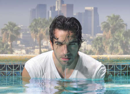 Sexy close-up portrait of a handsome man in glamorous swimming pool with city background Zdjęcie Seryjne