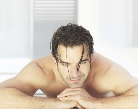male massage: Attractive man laying down in bright modern spa environment smiling waiting for treatments Stock Photo