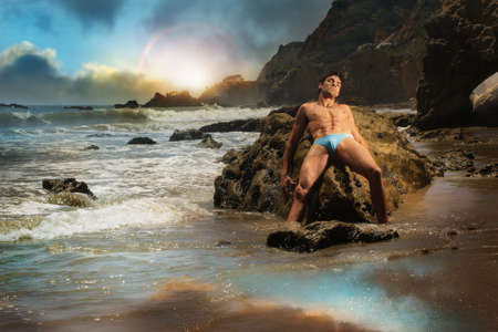 Beautiful young muscular male model laying on rocks in extotic stunning beach location Stock Photo - 14312782